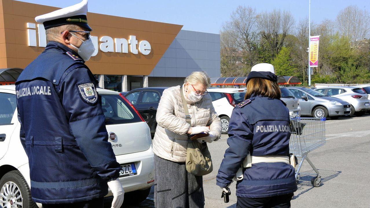 Unos agentes de la policía realizan controles a los consumidores en el exterior de un supermercado para verificar si cumplen con la nueva ordenanza municipal sobre compras que, para evitar colas, establece un  orden alfabético y durante días específicos de la semana en Cesano Boscone, cerca de Milán