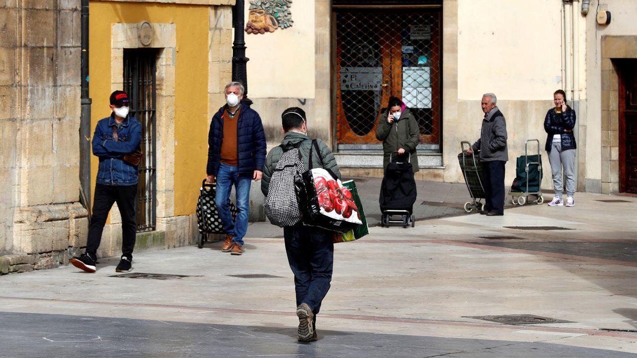 Primer día de uso obligatorio de mascarillas en Barbanza.Numerosas personas esperan para acceder a un supermercado hoy martes en la plaza del Fontán, de Oviedo