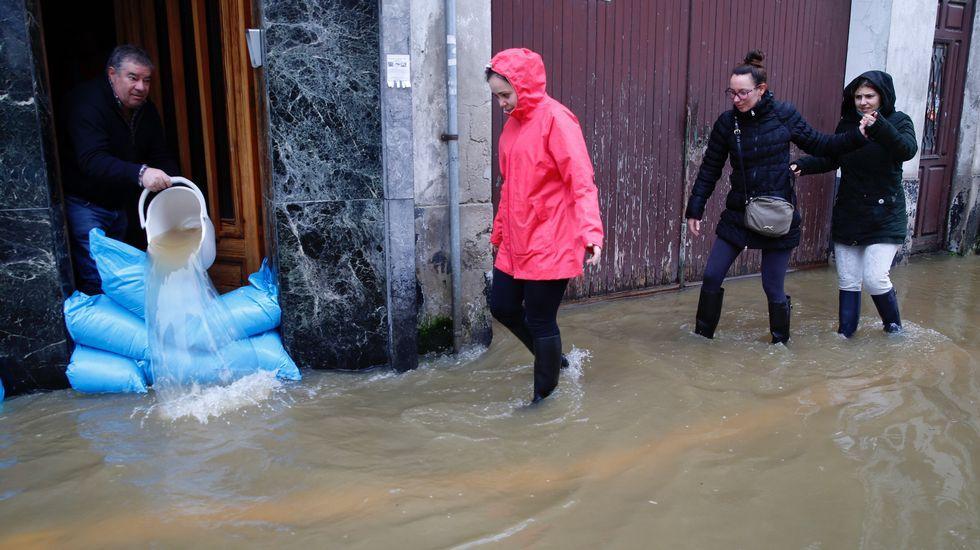 Vecinos de Sada sacando el agua de sus casas.