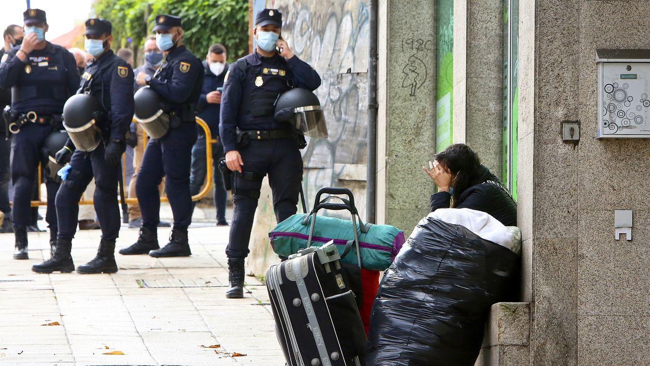 Primer fin de semana sin hostelería en Vigo.Imagen del desalojo con la policía custodiando la entrada ante una okupa con sus maletas