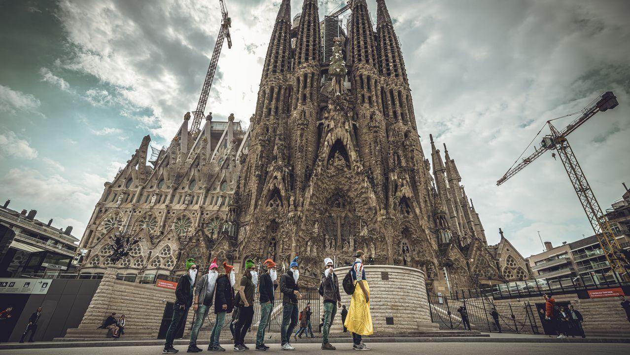 Turistas con mascarilla posan delante de la Sagrada Familia en Barcelona