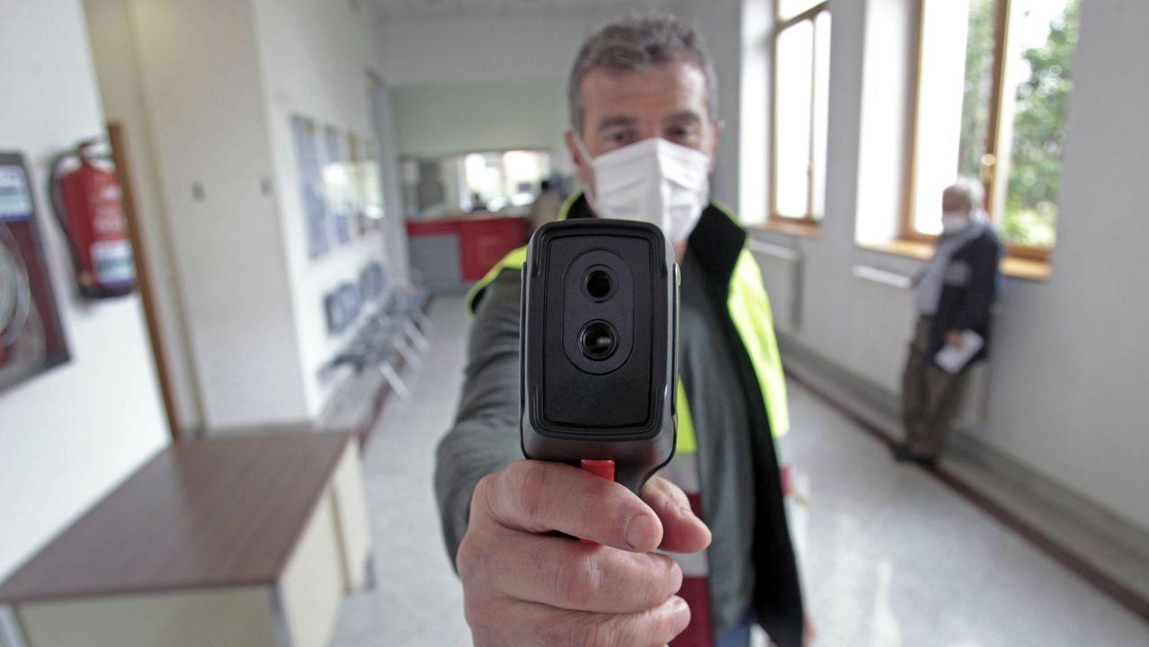 Un trabajador municipal, este lunes con el aparato que toma la temperatura corporal de quienes entran en el ayuntamiento de Monforte