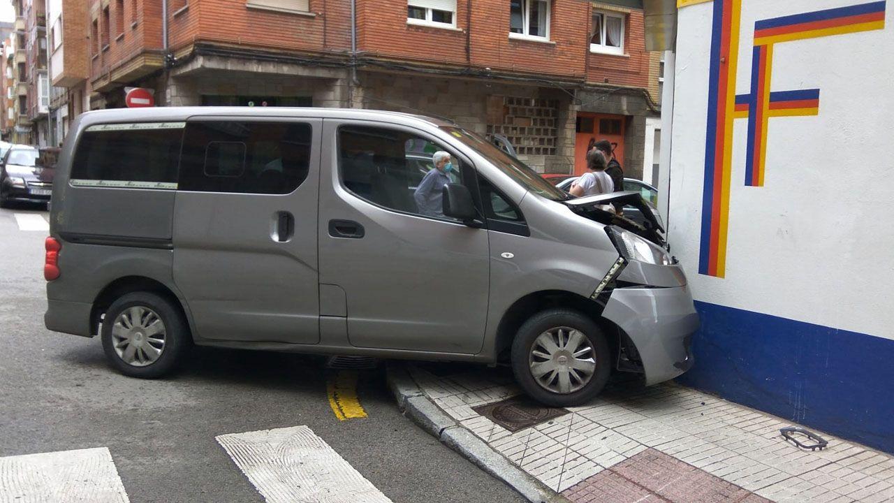 Furgoneta empotrada contra una tienda de pinturas, resultado del choque con otro vehículo, en Gijón