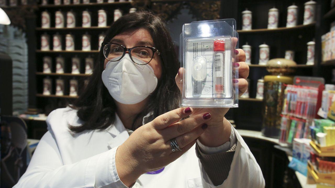 Nuevo incendio en la casa abandonada de Os Mallos.En la imagen, Carmen Álvarez Almodóvar, muestra el kit que se dispensa en las boticas para tomar las muestras en casa
