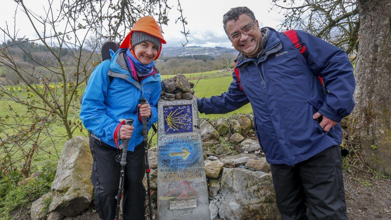 Dos peregrinos, en el mojón que marca los 100 kilómetros del Camino Francés