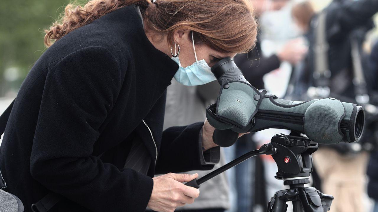 La candidata de Más Madrid, Mónica García, observa por una cámara durante su visita de este miércoles a la zona renaturalizada del Manzanares