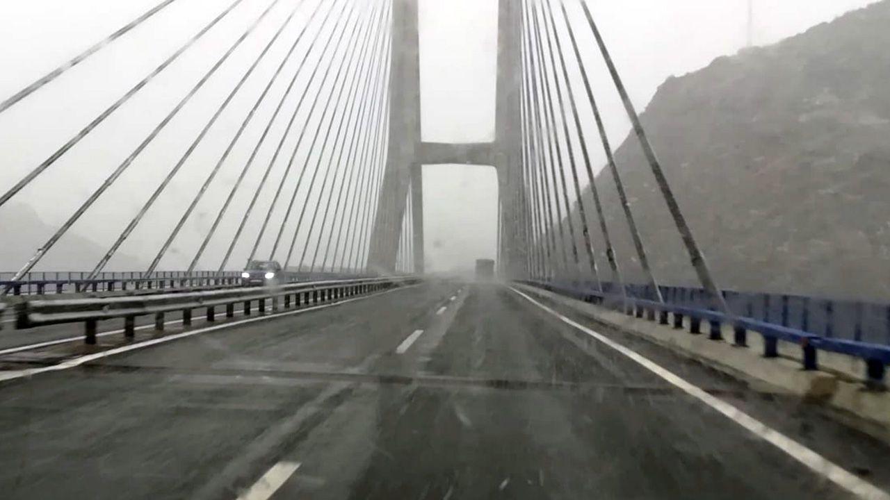 Los coches circulan entre una tenue nevada en la autopista del Huerna