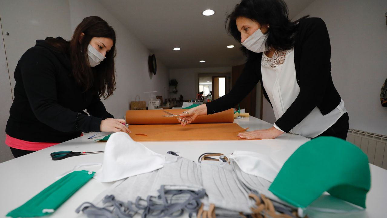 Miriam Bermúdez y Loli Polo, cortando este lunes tela para fabricar nuevas mascarillas contra el coronavirus en la escuela de costura de la segunda,en Covas (Viveiro)