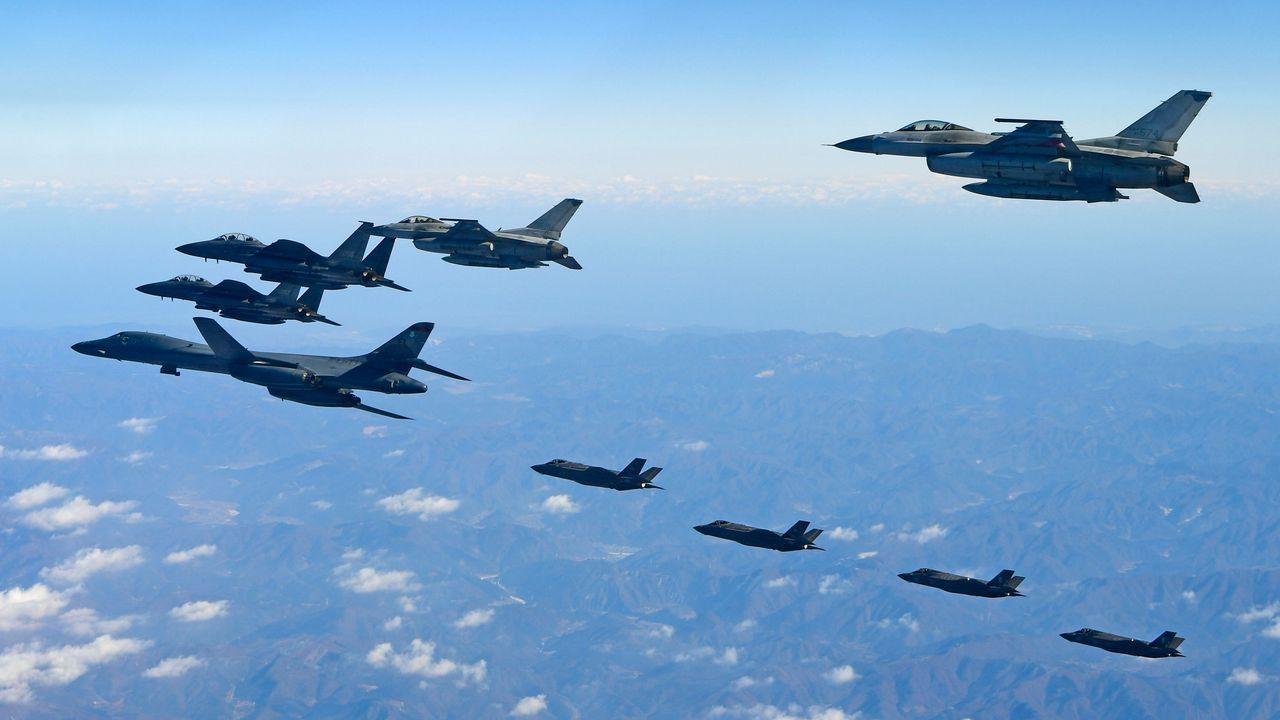 Un bombardero Lancer B-1B de la Fuerza Aérea de EE. UU. (izquierda), dos F-35A y otros dos F-35B (en segundo plano) sobrevuelan Corea del Sur con dos aviones de combate F-16 (derecha) y dos F-15K (arriba a la izquierda) surcoreanos durante un simulacro militar conjunto