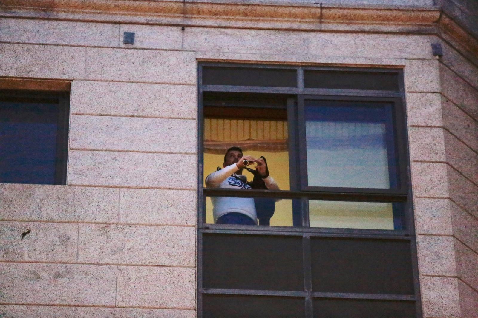 Un vecino de la avenida de Lugo, en Pontevedra, toca la gaita desde la ventana de su casa