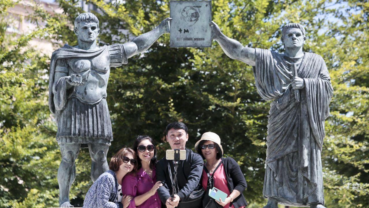 Un grupo de turistas posan ante la estatua en la que el emperador César Augusto entrega el legado a Pablo Fabio Máximo