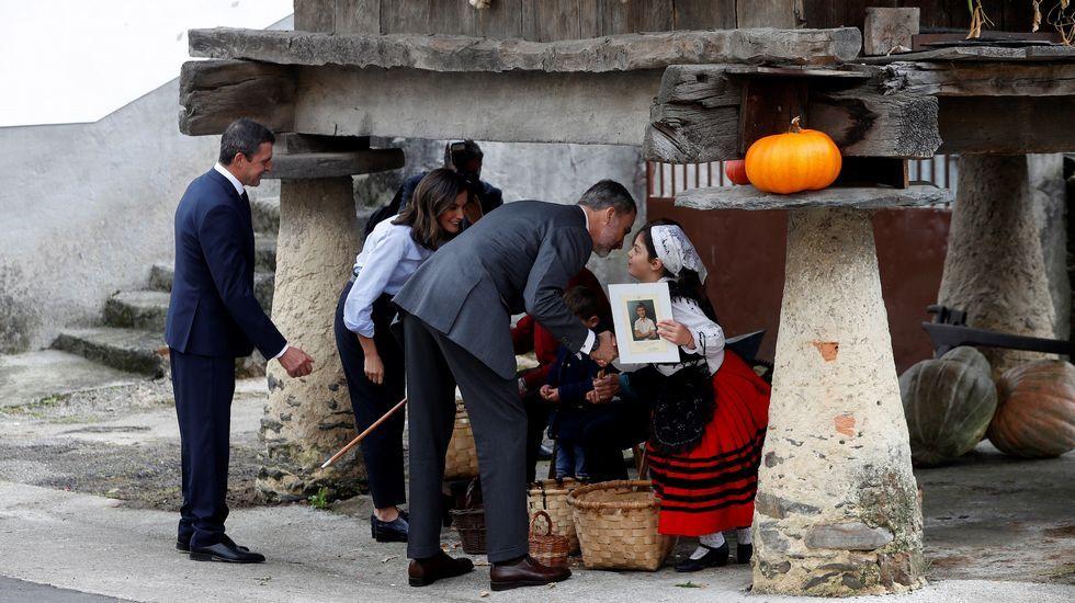 Los Reyes de España saludan a unos vecinos de Moal que elaboran productos típicos bajo un hórreo, durante su visita a la pedanía asturiana galardonada este año con el Premio Pueblo Ejemplar de Asturias