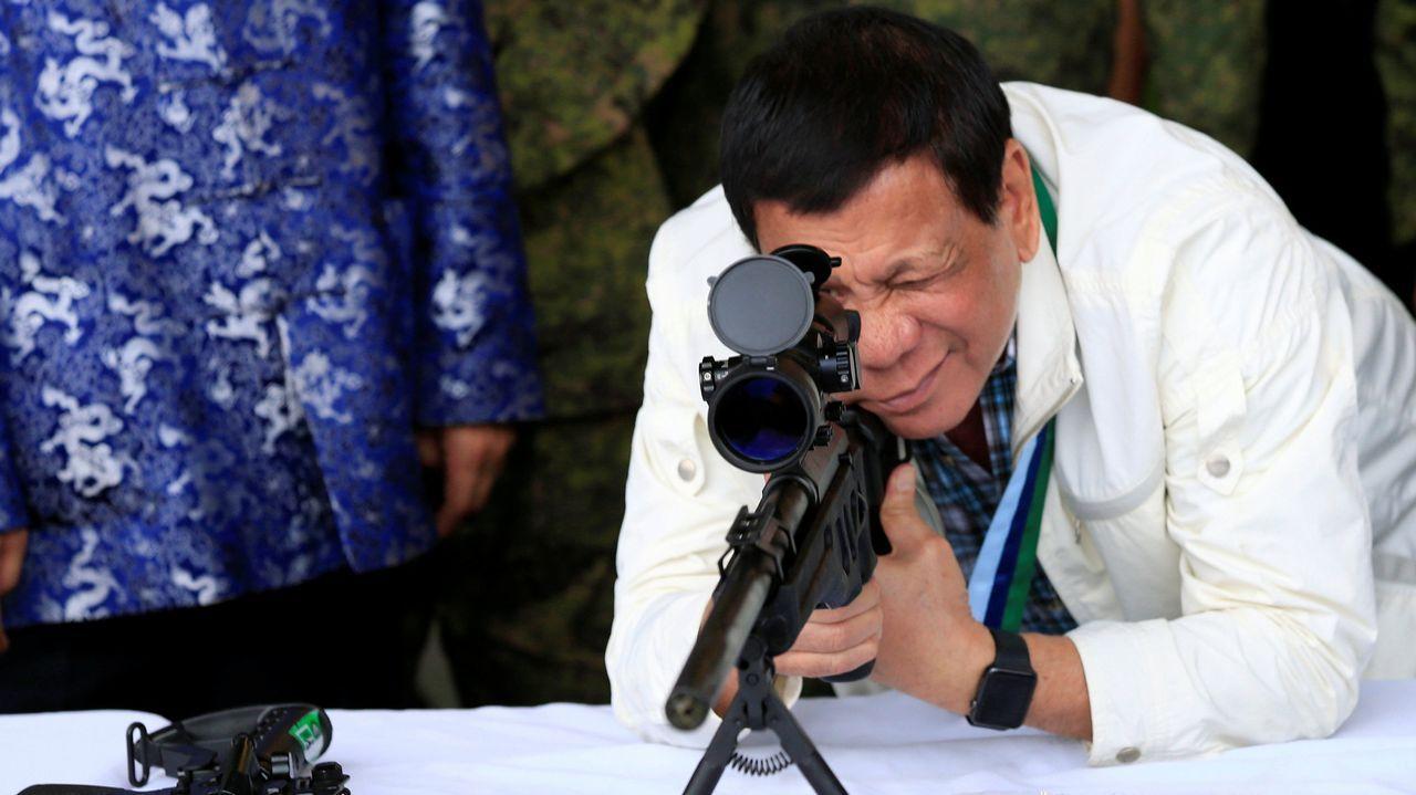 El presidente filipino Rodrigo Duterte chequea la mirilla de un rifle de francotirador durante una ceremonia militar.