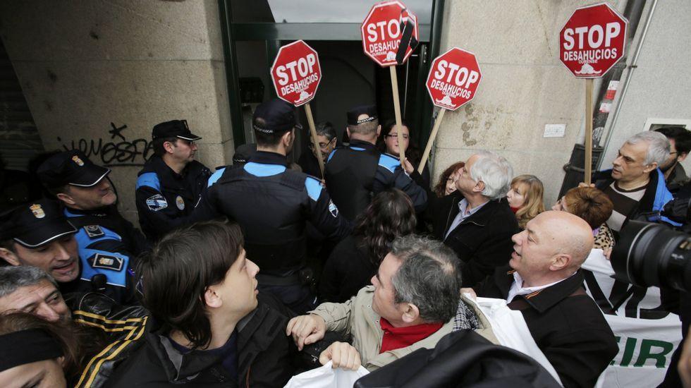 Policía y activistas de Stop Desahucios en el desahucio de una mujer en Ourense.