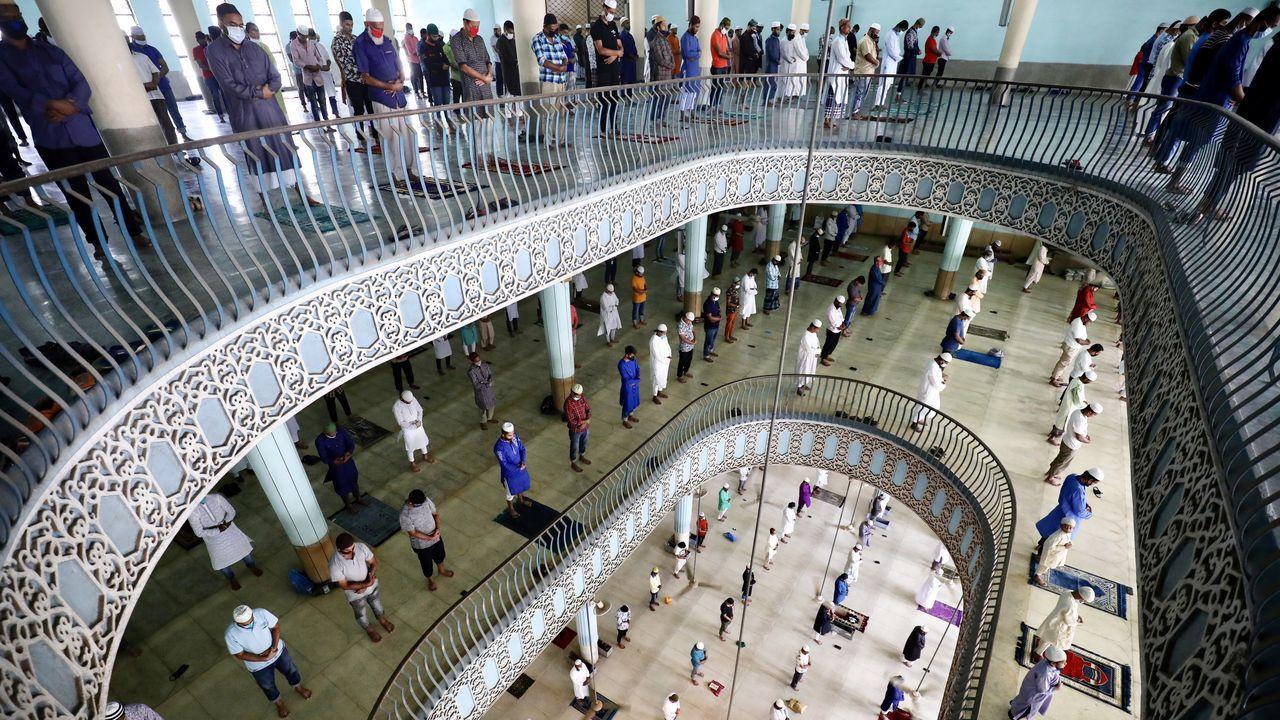Fieles musulmanes rezan en una mezquita de Dhaka. Muchos de ellos visten mascarillas