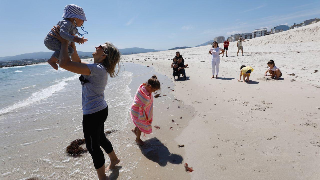 Padres paseando con los niños por la playa de A Rapadoira de Foz