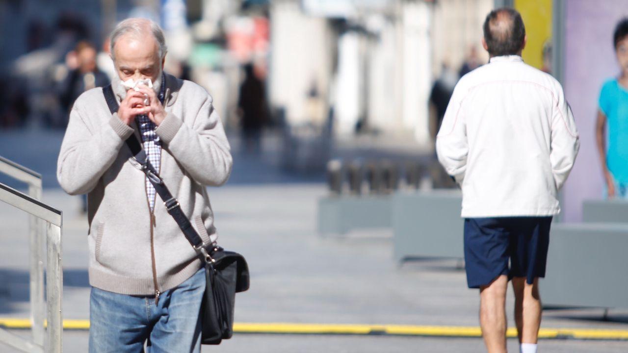 Vigo paraliza sus obras por el coronavirus.Un hombre con mascarilla paseando en Vigo este sábado