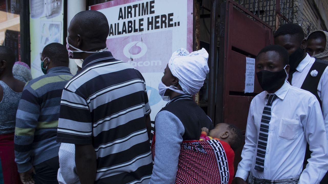 En Pretoria, Sudáfrica, ciudadanos, algunos con mascarillas, aguardan para recibir comida