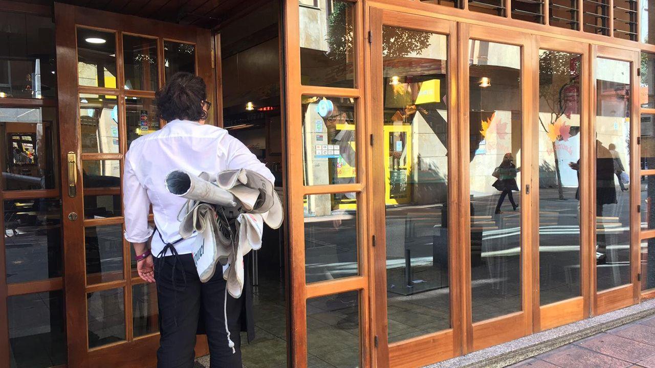 Una de las trabajadoras de una cafetería, metiendo la sombrilla, antes de cerrar