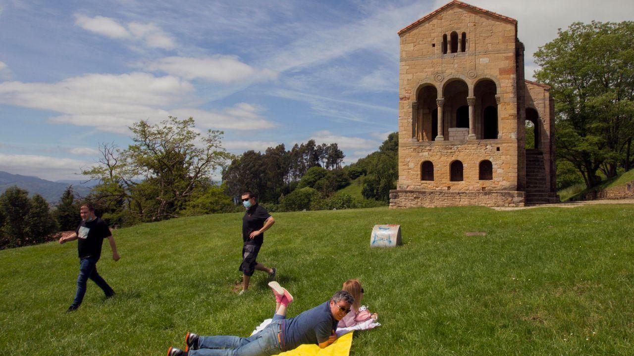 Varias personas toman el sol este domingo ante el monumento prerrománico asturiano de Santa María del Naranco en Oviedo.