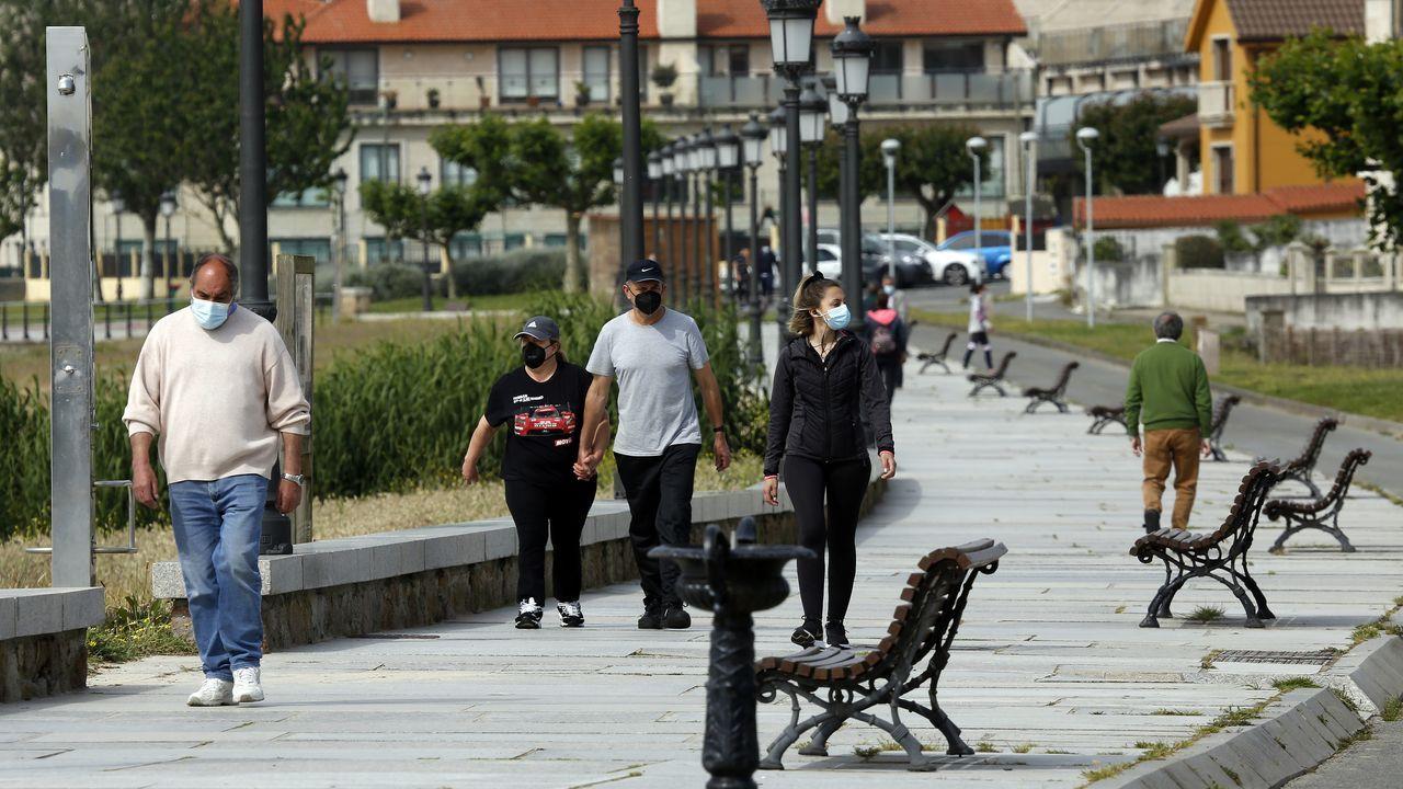 Gente con mascarilla paseando por el paseo de Coroso en Ribeira