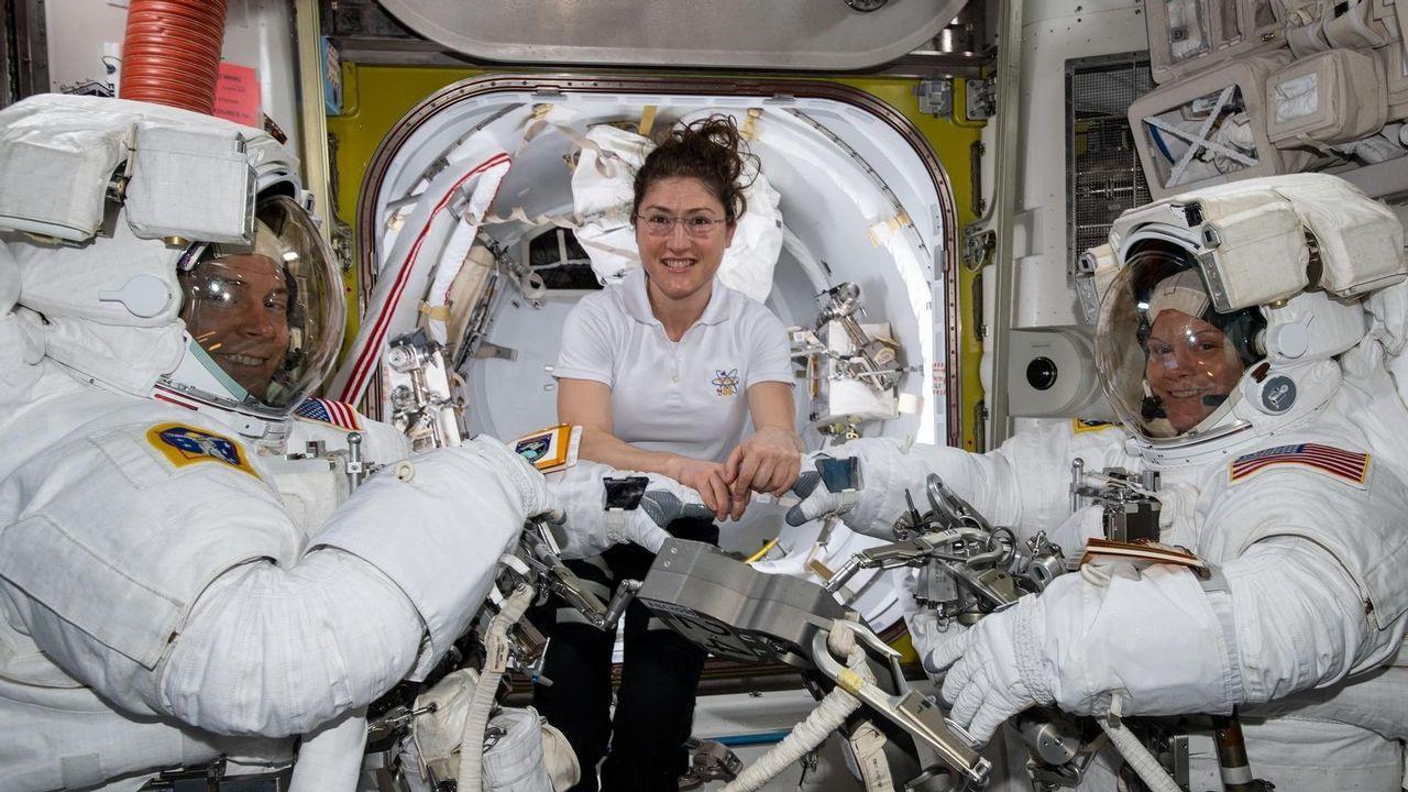 La astronauta de la NASA Christina Koch (centro) ayuda a sus compañeras, Nick Hague (izquierda) y Anne McClain (d) con sus respectivos trajes