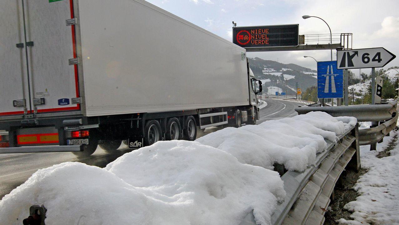 Un camión pasa entre los márgenes de la carretera cubiertos de nieve, en el concejo de Lena
