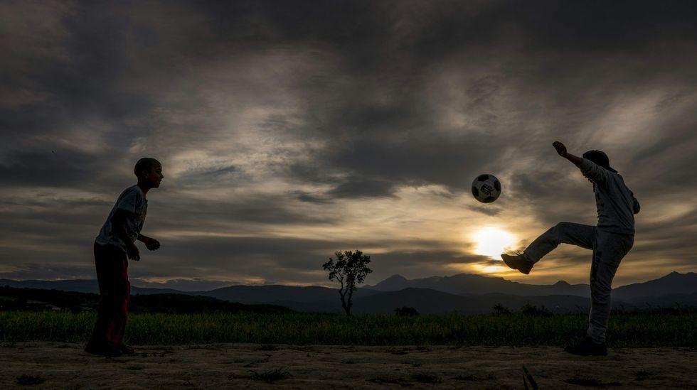 Dos niños jugando al fútbol durante la puesta de sol