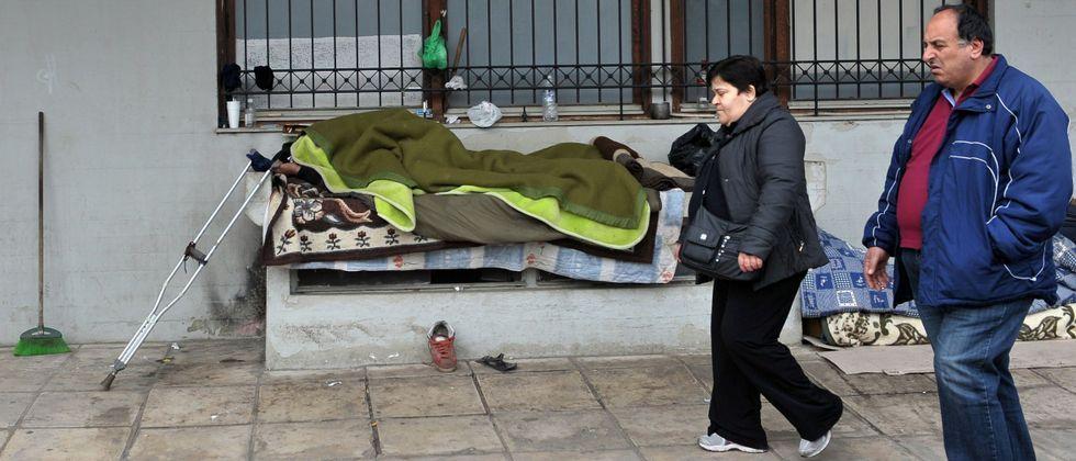 Dos personas con la vista en el suelo caminan por una calle donde descansa un sintecho en la ciudad de Salónica.