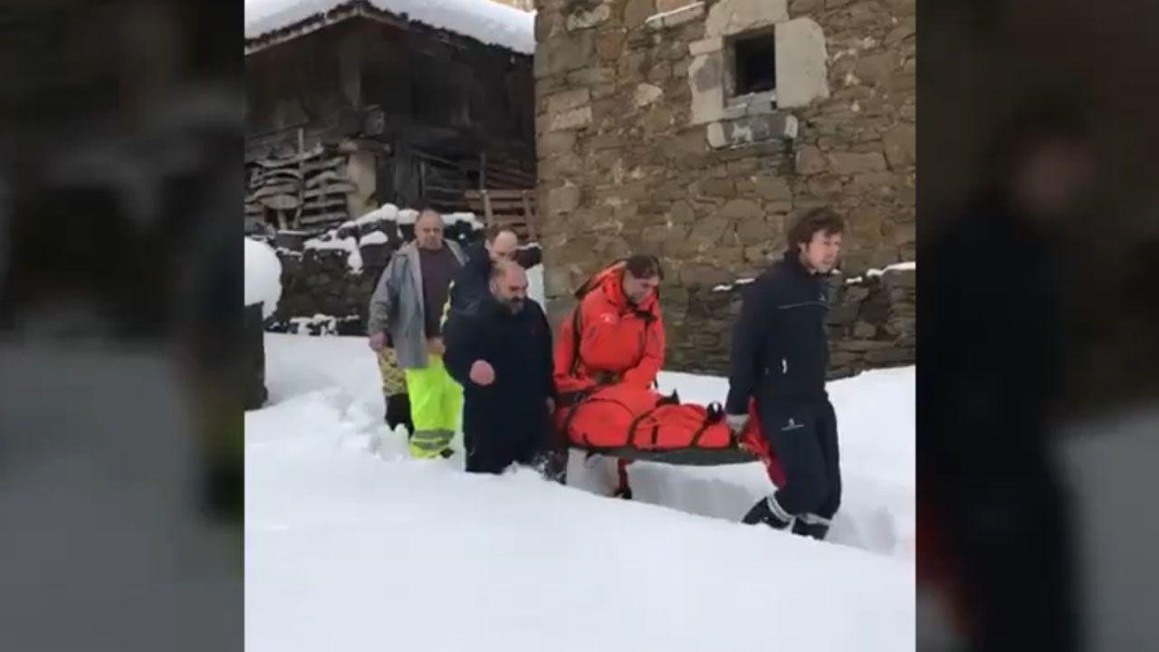 Rescate y asistencia sanitaria en Caso. Vecinos de Pajares (Asturias) retiran nieve del tejado de su casa de 300 años, una de las más antiguas del pueblo.
