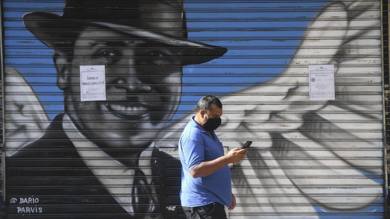 Un hombre pasea en Buenos Aires junto a una valla con un retrato de Gardel