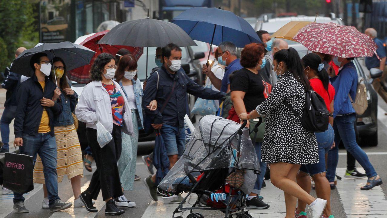 colegio Jacinto Benavente Gijón.Personas pasean con paraguas en mano por Oviedo