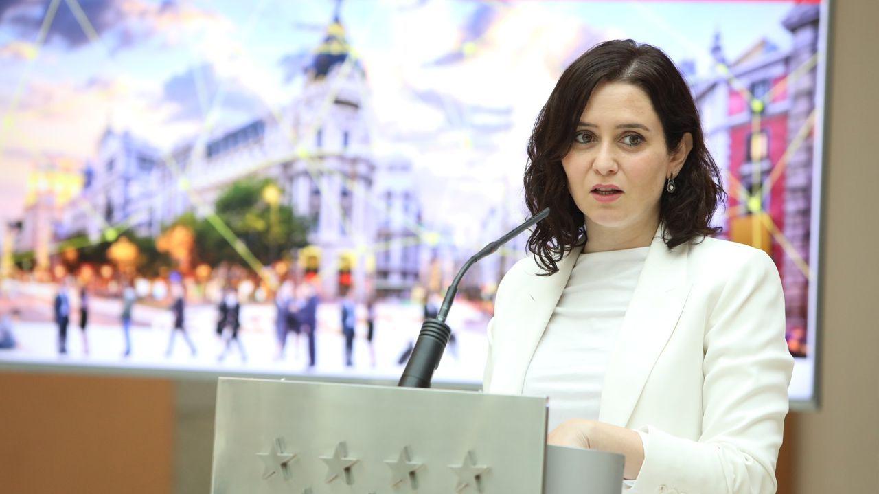 La presidenta de la Comunidad de Madrid, Isabel Díaz Ayuso (d) conversa con la portavoz de Vox en la Asamblea, Rocío Monasterio