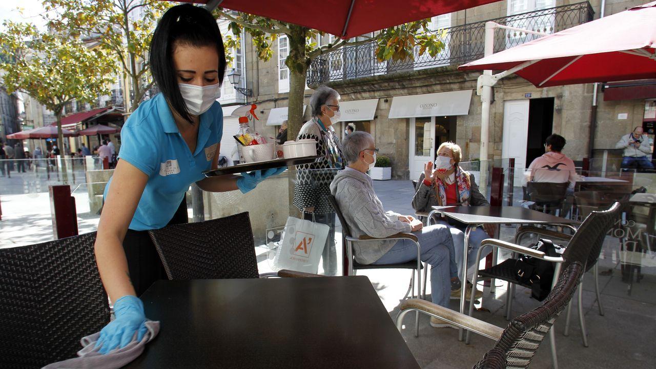 Una camarera limpia una mesa en una terraza de la calle Cardenal de Monforte, abierta hoy por primera vez en dos meses