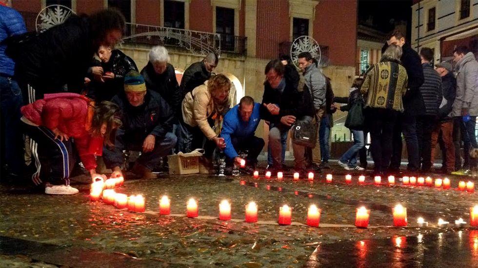 Varias personas encienden velas por las víctimas del VIH en la plaza Mayor de Gijón