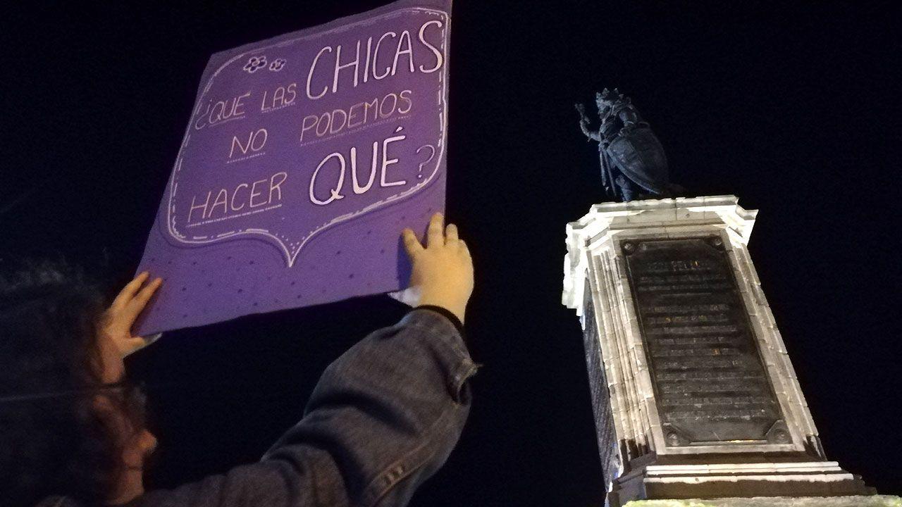 Una joven sostiene un cartel ante la estatua del rey Pelayo