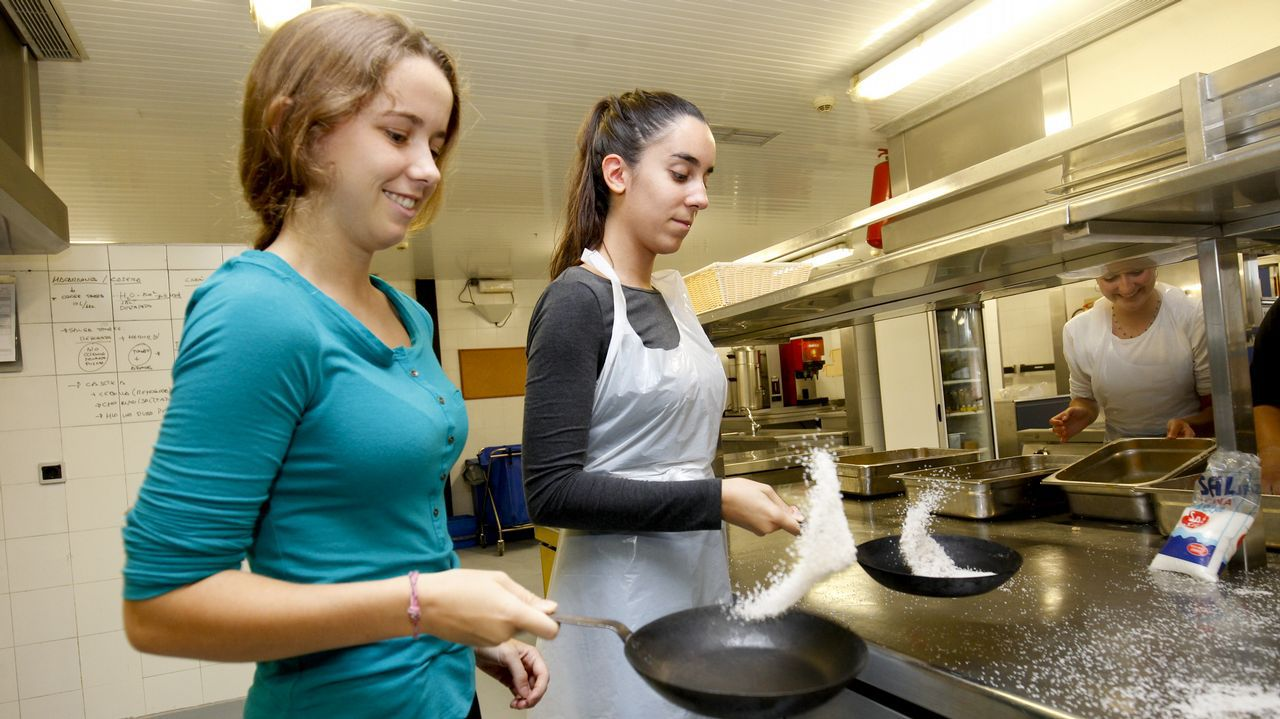 Dos jóvenes aprenden a voltear sartenes con sal gruesa. Quien más sal derrame, pierde