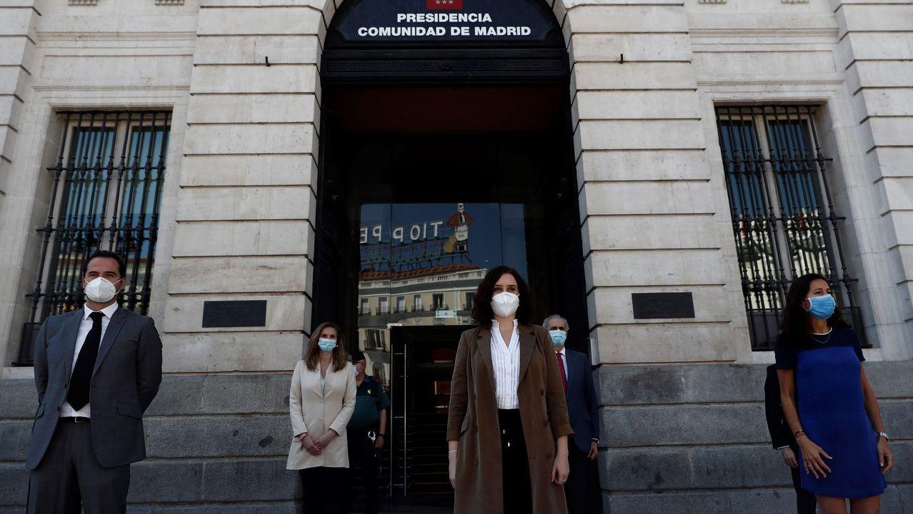La presidenta de la Comunidad de Madrid, Isabel Díaz Ayuso (c), y el vicepresidente Ignacio Aguado (i), junto al resto de miembros del Gobierno regional se congregan a las puertas de la sede de la Presidencia de la Comunidad de Madrid para guardar un minuto de silencio en memoria de los fallecidos por el covid-19