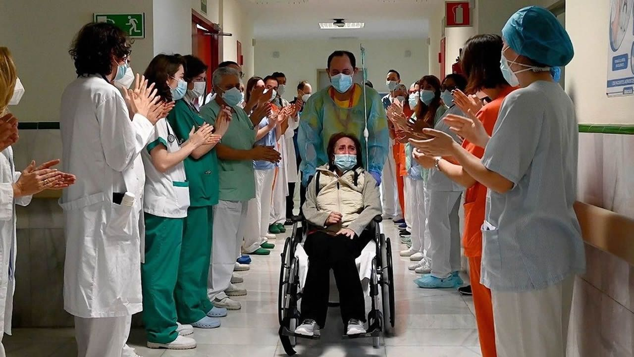 Elsa Lomas abandona el hospital entre los aplausos del personal sanitario.En Manaos, Brasil, un indígena se prueba ante el espejo una mascarilla protectora