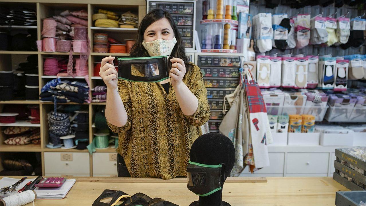 Montse Gómez, sujetando una mascarilla para sordos en su mercería carballiñesa, La Moderna