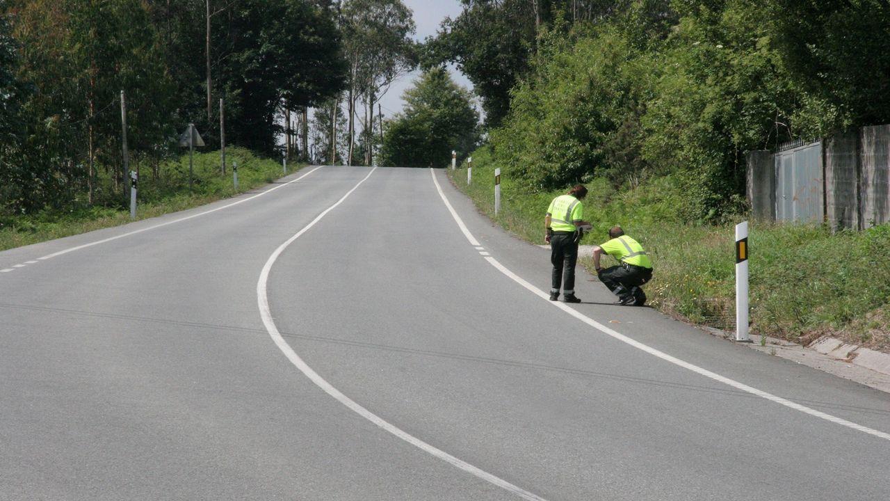 Dos guardias civiles buscan pruebas en una carretera de Abegondo, en el lugar en el que un ciclista fue atropellado por un conductor que se dio a la fuga