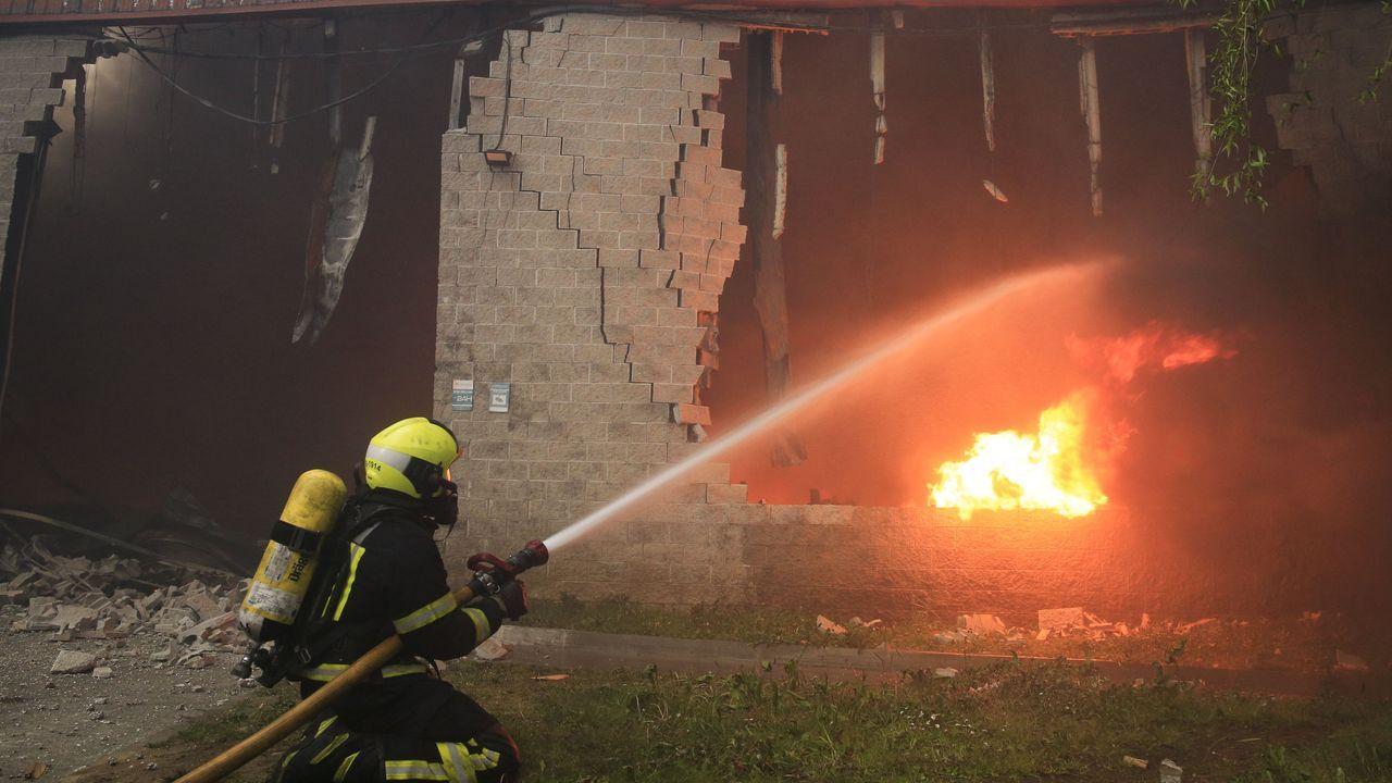 Un bombero se enfrenta a las llamas en una de las naves calcinadas