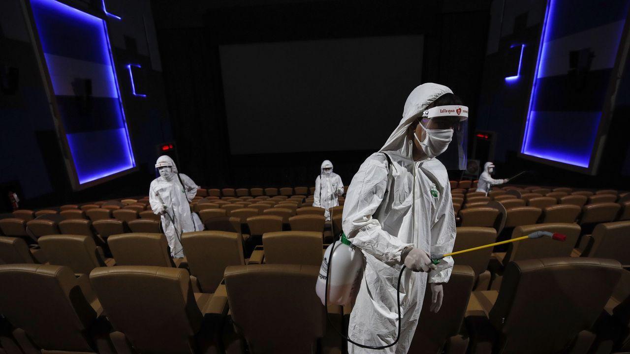 Trabajadores desinfectan un teatro en Bangkok antes de su reapertura