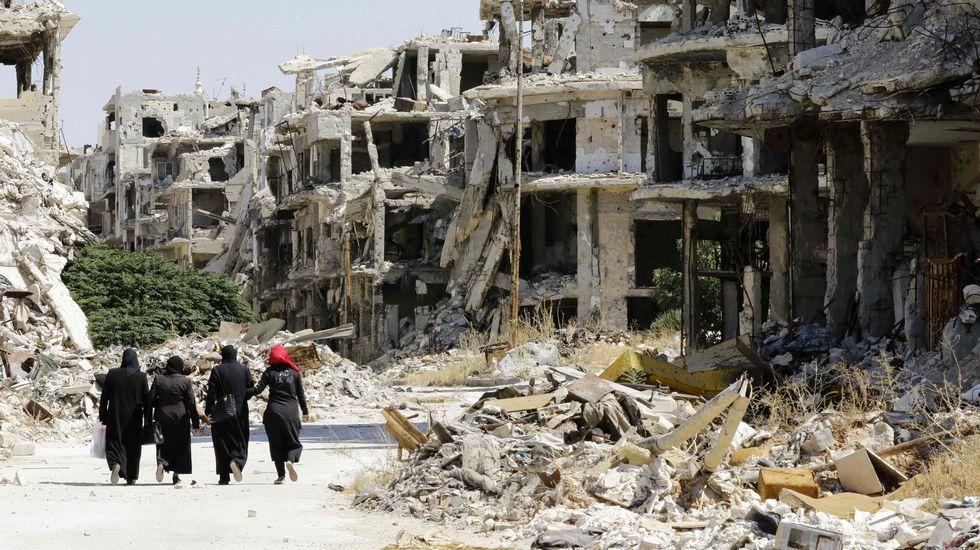 Graban ataques con bombas de fósforo sobre Alepo.Mujeres pasan entre los edificios destruidos en el barrio de Jouret al Shiah, en Homs.