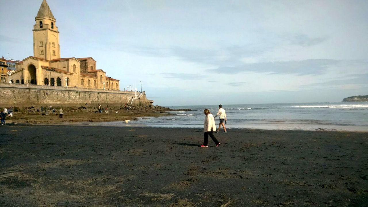 Nubes negras tras el fuerte viento sobre el puerto de Gijón.Mancha de carbón en la playa de San Lorenzo