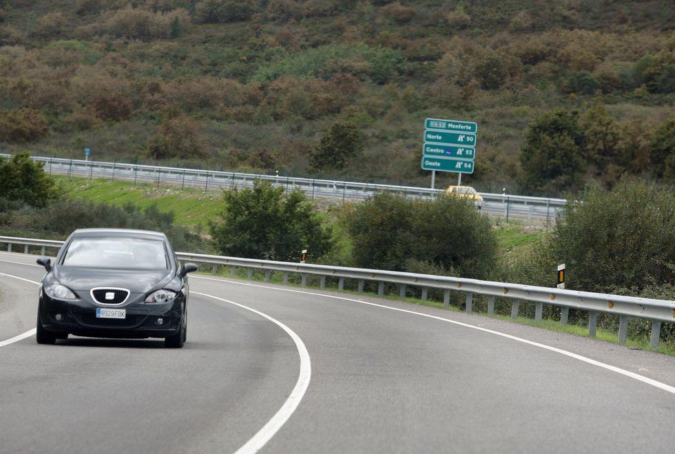 Un coche circula por la LU-546 entre Ribas Altas y A Áspera, con el trazado de la vía rápida al fondo.