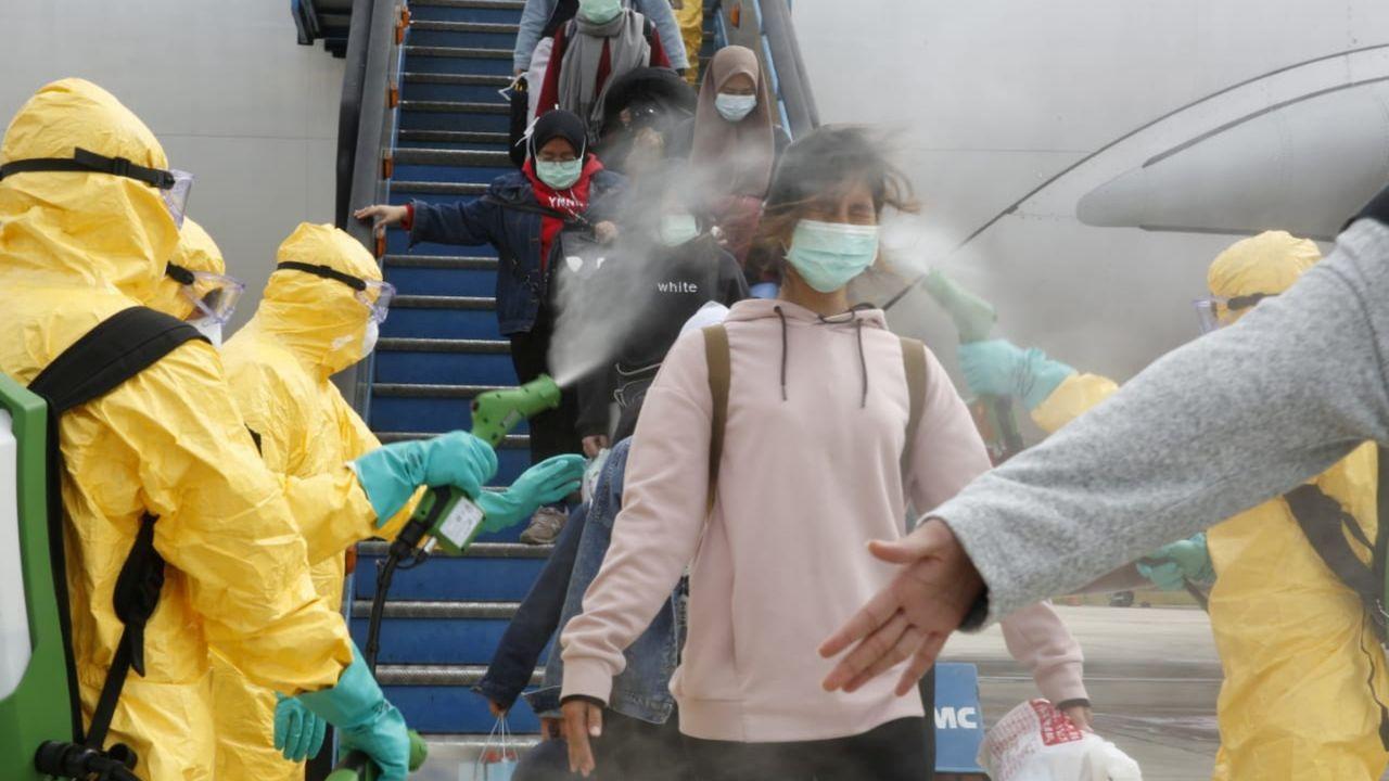 Así es una cuarentena paradisíaca.Personal médico de Indonesia rocía con antiséptico a los repatriados llegados de Wuhan.