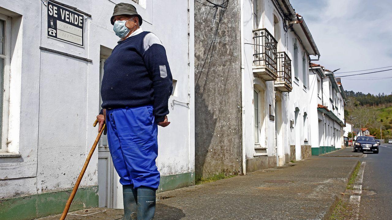 Un hombre pasea con su bastón por Ponte de Mera, donde solo quedan una farmacia y un estanco