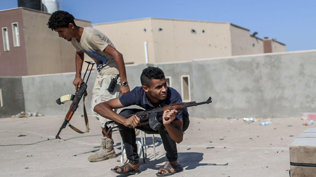 Los combatientes del Gobierno de Serraj  se cubren del fuego enemigo en la línea del frente de A Khalla