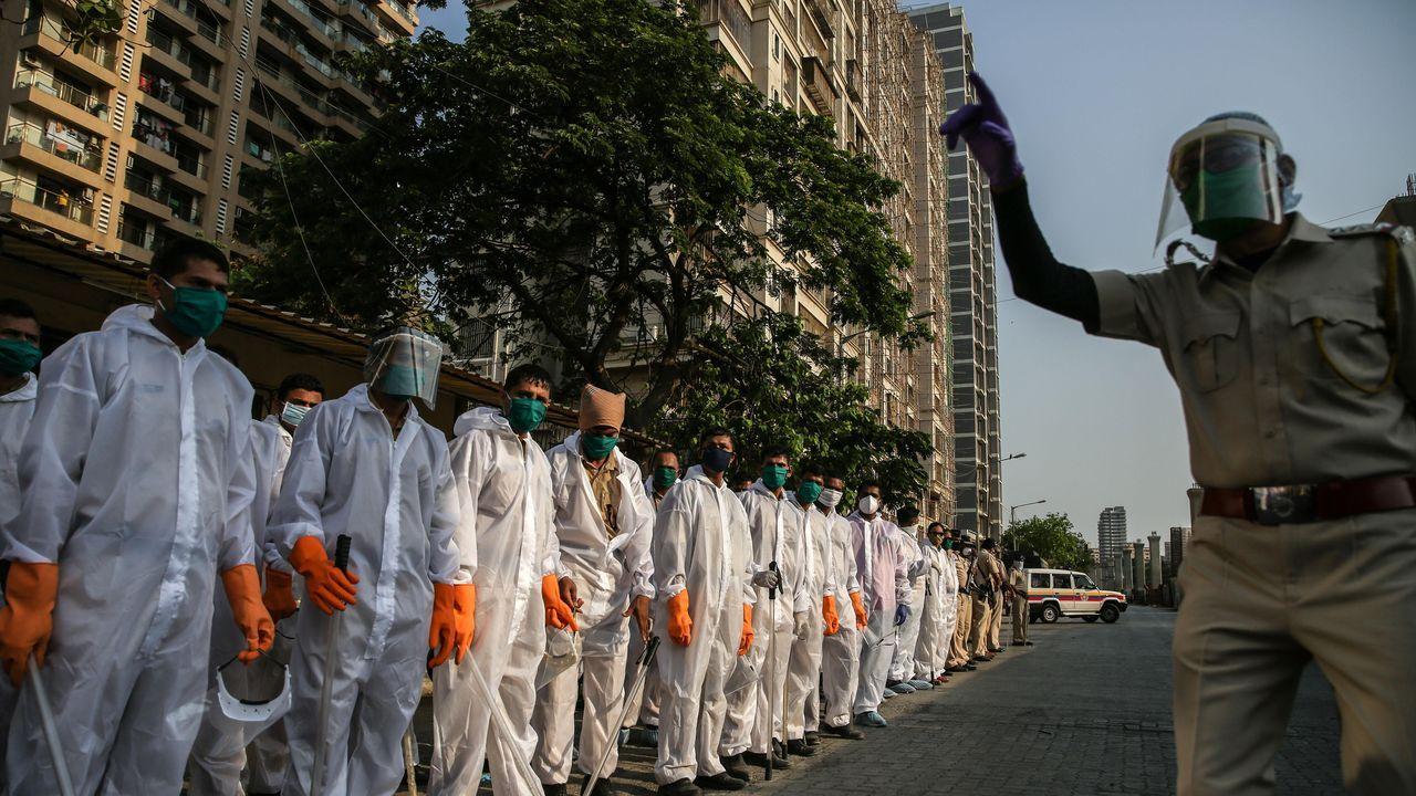 Un oficial explica a agentes de la policía india cómo emplear los trajes de protección, en las calles de Mumbai